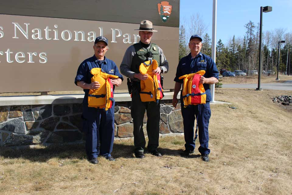 Three men standing in front of Voyageurs National Park sign each holding a youth life jacket.