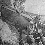Historic photo, man sitting on rocky shoreline writing in a journal with boat pulled up next to him.