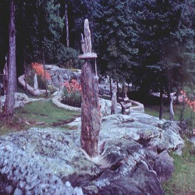 A small chair made out of stone sits atop a pillar of rock, with beds of orange lilies in the background.