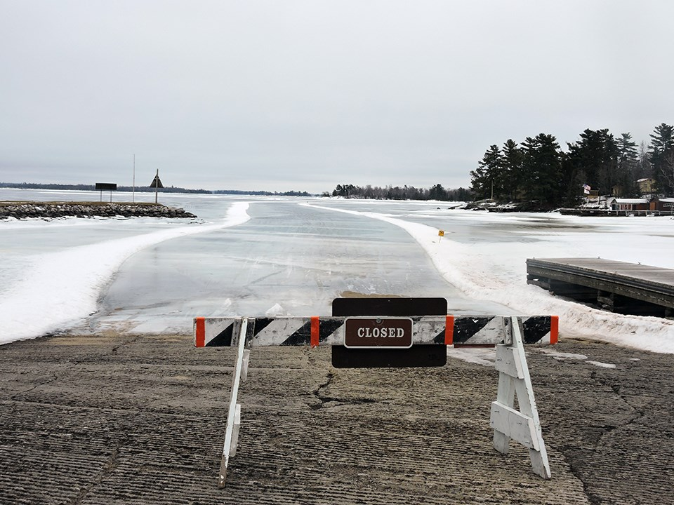 "A sawhorse with a sign reading ""CLOSED"" stands in front of a long, road-like stretch of ice on a frozen, scenic lake."