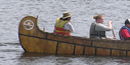 Park volunteer, Ida Mainville steers a canoe full of modern-day voyageurs.