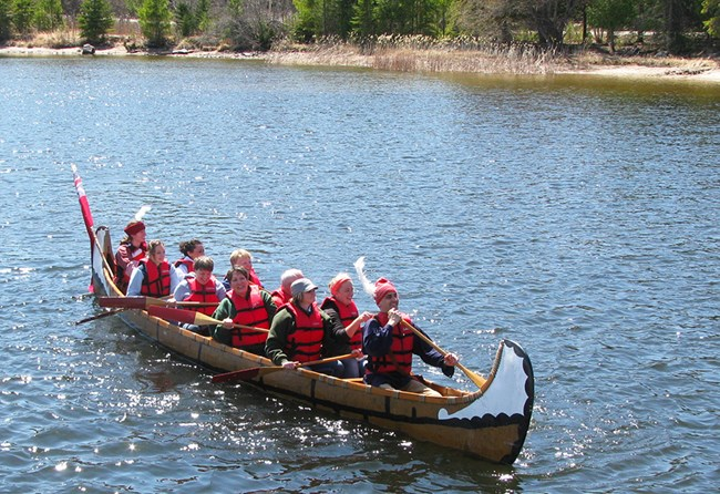 A group of ten adults (some in historic costumes and hats) laugh and paddle a large birch bark canoe on a scenic lake.