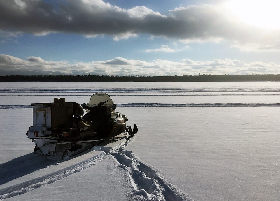 A white snowmobile with a large box bolted to the back faces toward the wide expanse of a frozen lake, with a forested treeline on the horizon.