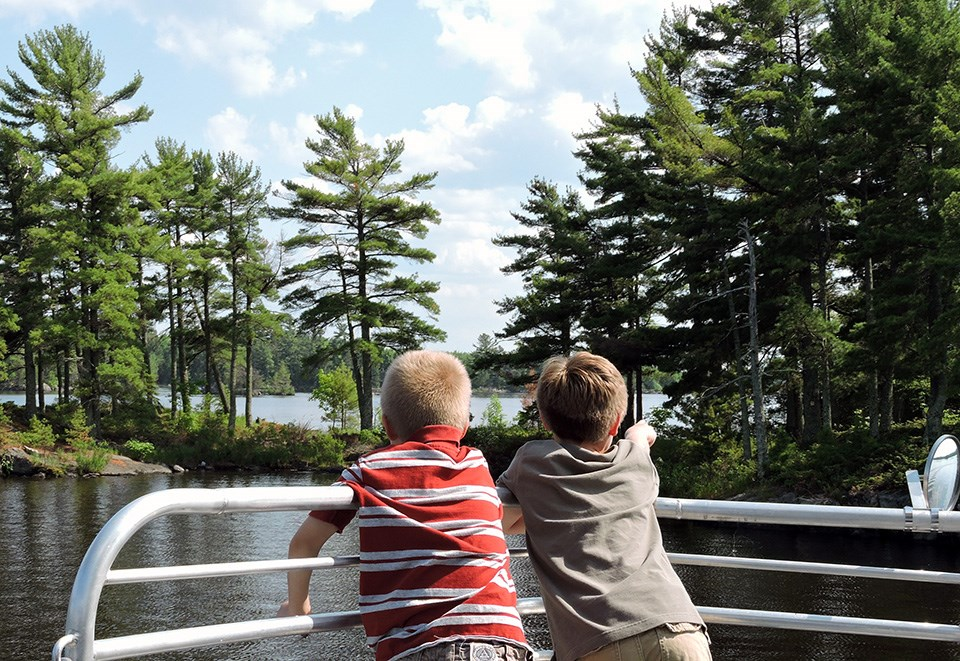 Two kids stand side by side by a tour boat railing looking out towards a scenic lake shore lined with trees. One boy points to something on the shoreline.