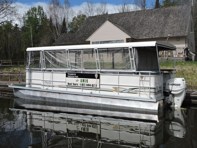 "A metal pontoon boat labeled ""Amik"" is moored at docks in front of the Kabetogama Lake Visitor Center."