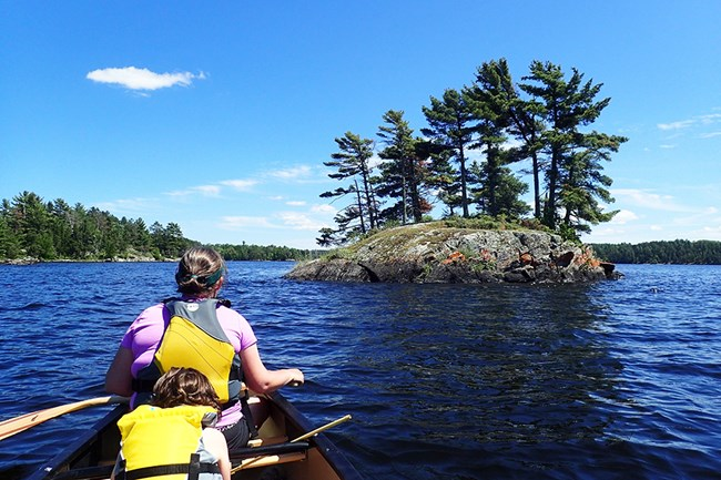 An adult and child in yellow life jackets sit at the front of a canoe on a scenic lake, looking towards a tree-lined island.