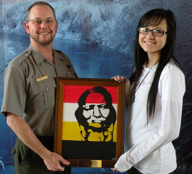 Rachael Shockley, a junior at Elk City High School, donates her painting of Cheyenne Peace Chief Black Kettle to Washita Battlefield NHS.  She is shown here with Park Superintendent, M. Tucker Blythe.