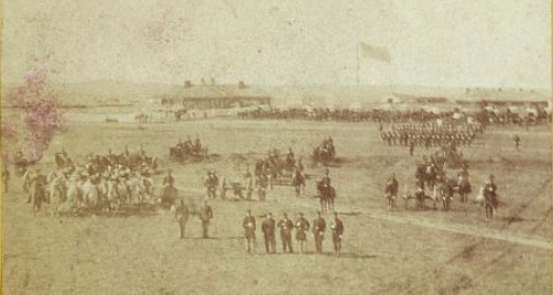 Fort Harker, Kansas. From 1860's photograph, shows soldiers posing in the foreground. In background is a barracks with the American flag overhead. Setting is on the Great Plains.