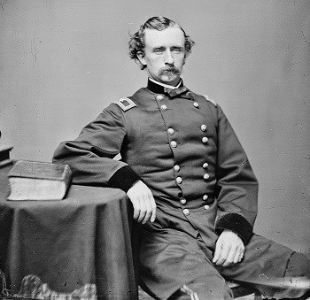 George Armstrong Custer, 1864 photograph showing him seated with right elbow resting on table.