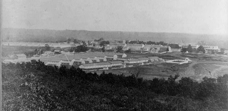 Fort Leavenworth Kansas, 1867, shows a neat row of barracks nestled at the bottom of a hill in a valley on the Great Plains.