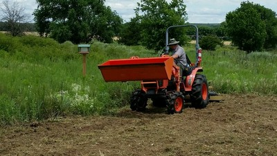 Park Rangers using a Kubota tractor to prepare the ground for planting seeds in the fall.