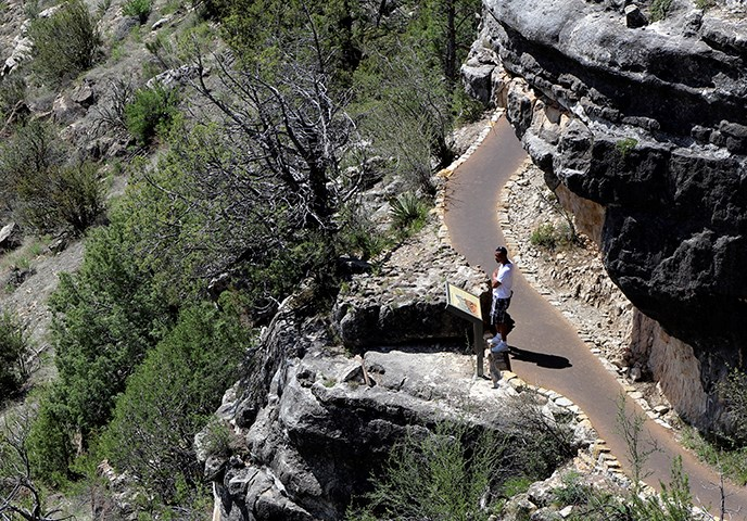 A lone visitor gazes out over Walnut Canyon from a park trail beneath the rim