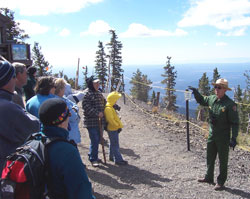 A ranger talks to visitors on mountaintop.