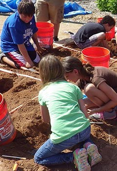 Students digging for replica fossils.