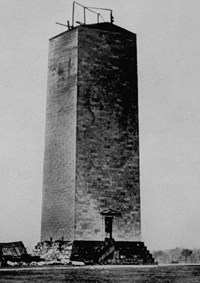 The partially completed lower portion of the Washington Monument with construction equipment on top.