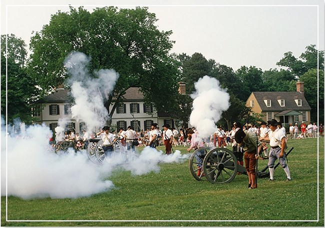 A crowd watching a cannon demonstration by historic reenactors on a grass field near historic brick buildings