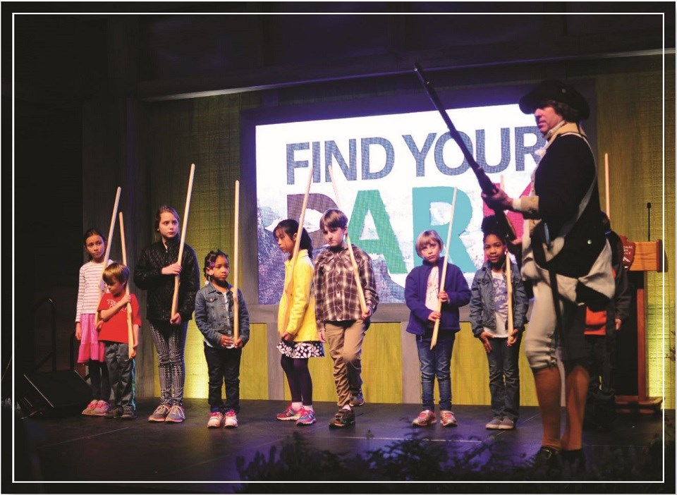 "Eight children standing in a line holding replica muskets on a stage in front of a sign reading ""Find Your Park"". A man in period clothes holds a replica musket while standing in front of a podium."