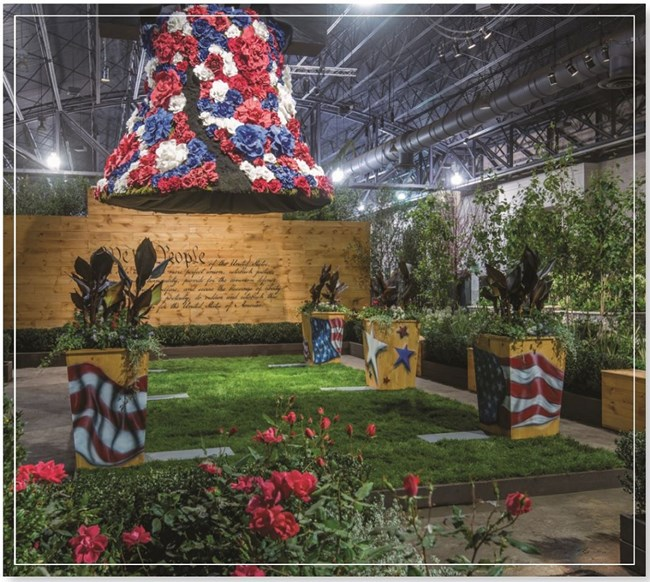A liberty bell replica covered in red, white, and blue flowers is mounted over a small grassy area with several planters painted with colorful patriotic designs. The preamble of the Constitution is written on a wall as a backdrop.