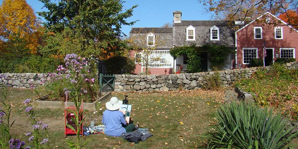 Artist painting in front of the Burlingham House