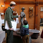 A student and park ranger touch a reproduction sculpture in the Young Studio.