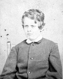 A black and white photo of a young boy sitting.