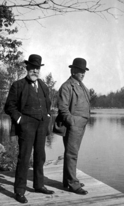 A black and white photo of two men standing on dock in winter.