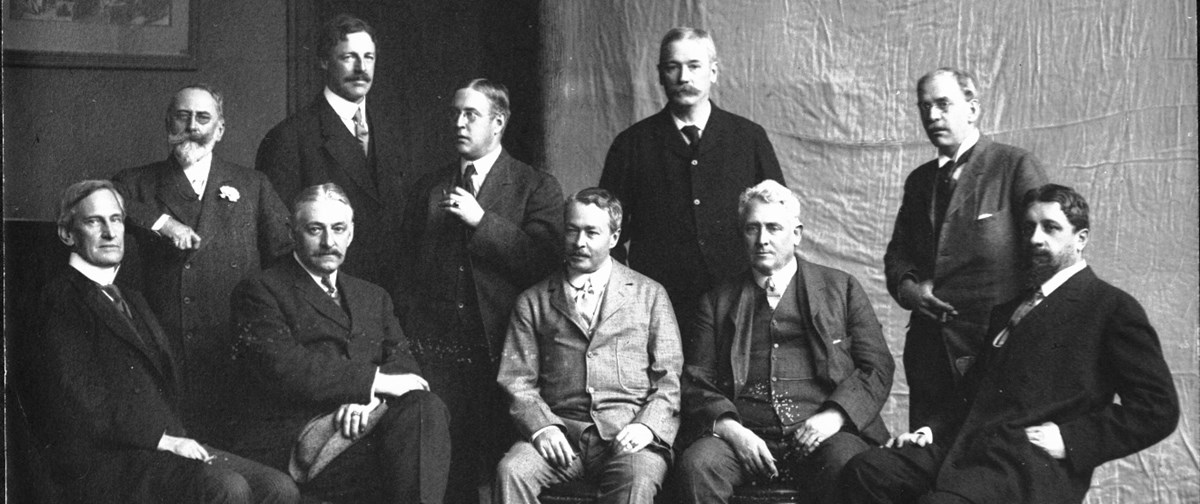 A black and white group photo of ten men, some standing while others sit.
