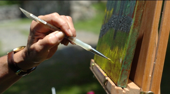An artists paints outdoors in Weir Farm National Historic Site's landscape.