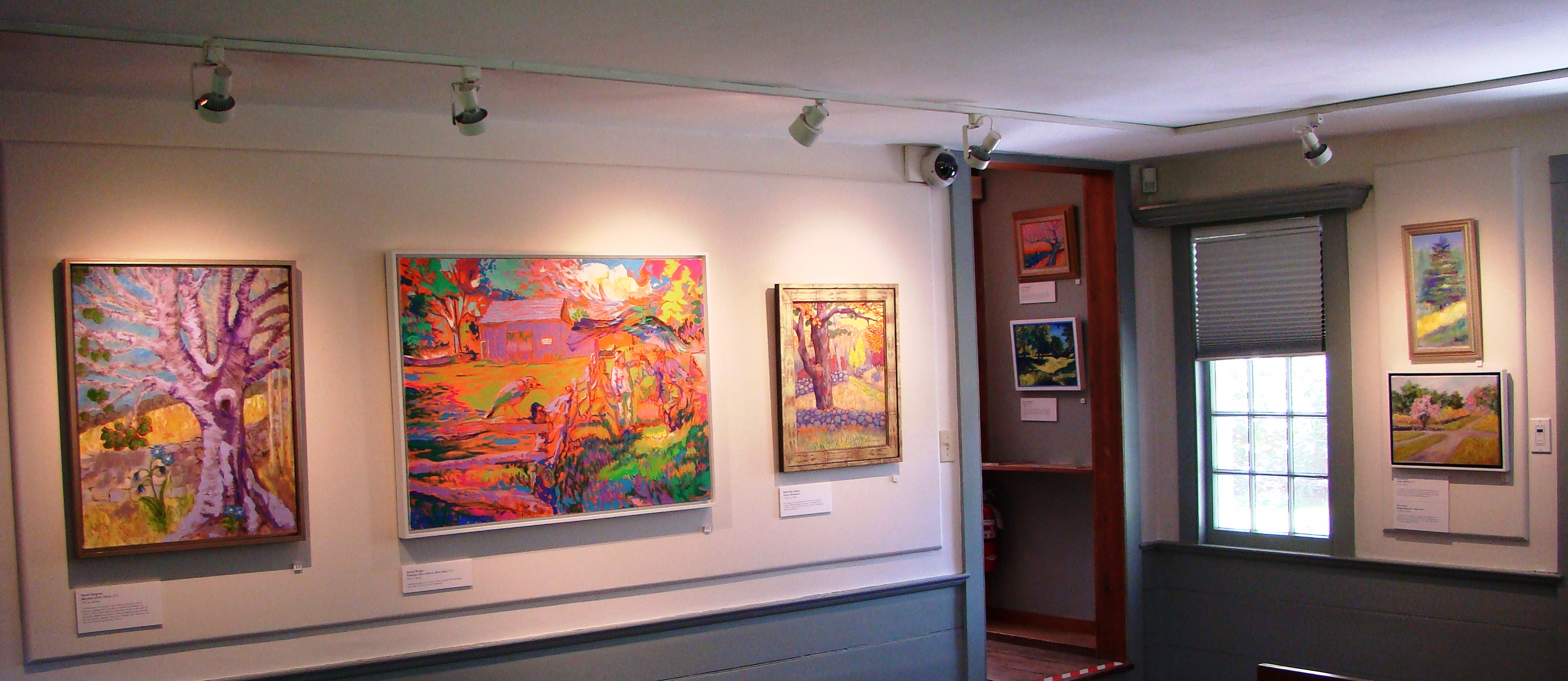 Several brightly colored landscape paintings against a white gallery wall.
