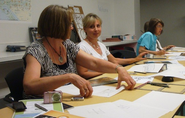 Image of three teachers working on a drawing during an teacher workshop at the White House Visitor Center.