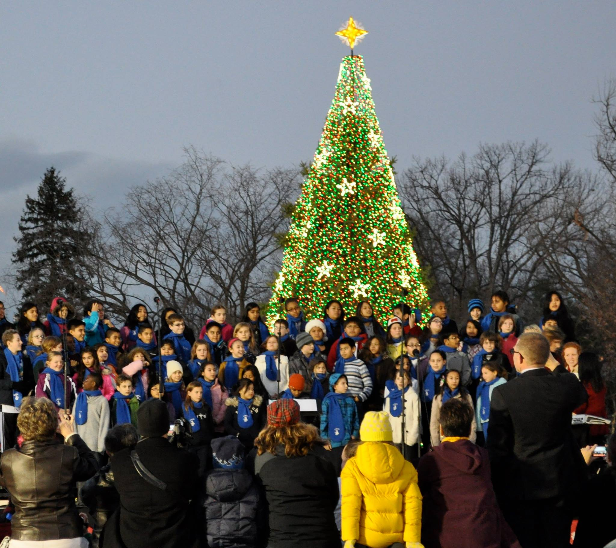 A choir sings in front of the National Christmas Tree, during the 2013 music program, while visitors take pictures