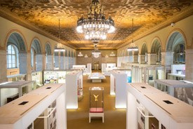 Modern exhibits are arrayed in a large room with an ornate ceiling and light fixtures
