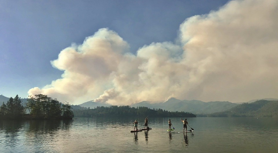 Four paddleboarders on Whiskeytown Lake looking at smoke from fires in the distance