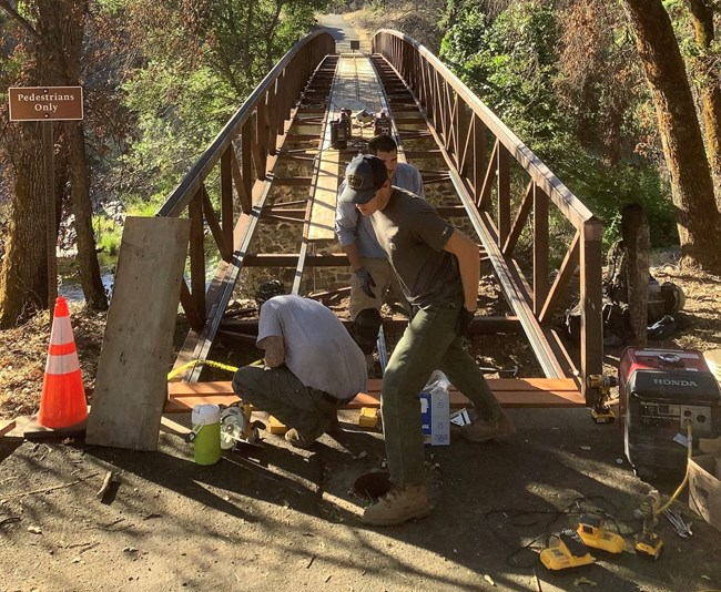 Park maintenance staff rebuilding the main footbridge within Tower House Historic District.