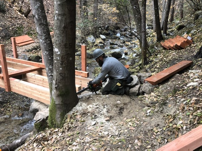 Park maintenance staff finishing up the construction of a new footbridge near Whiskeytown Falls. The former footbridge burned in the fire. NPS Photo.
