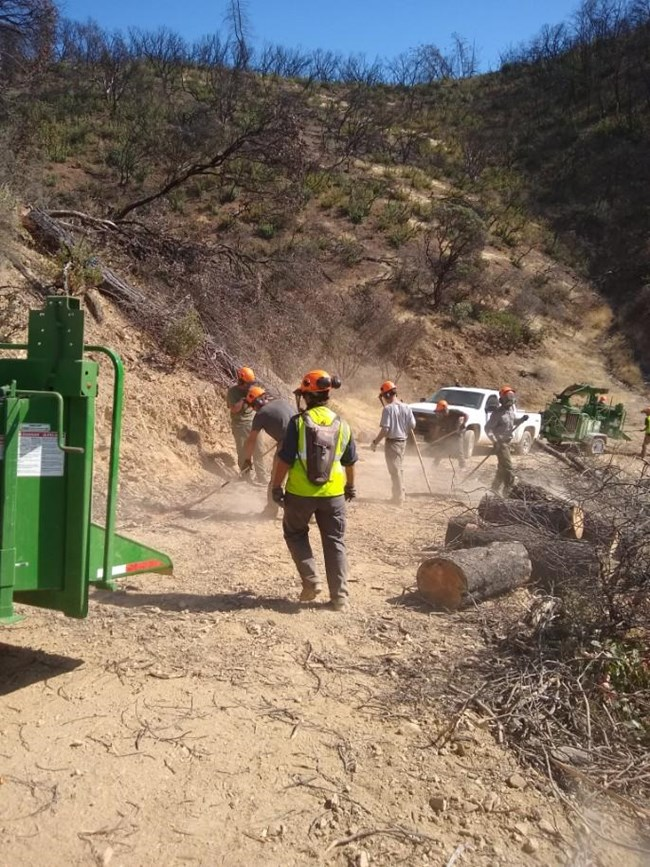 Park maintenance staff removing dangerous hazard trees from South Shore Drive as part of the post-Carr Fire reopening effort. NPS Photo.