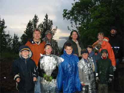 Rain soaked Scouts and adults after completion of Native Plant garden weed picking with lake in background