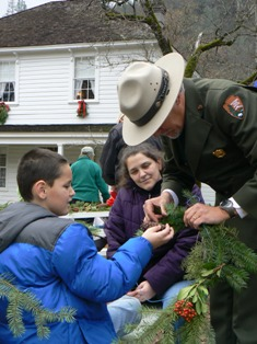 Superintendent Jim Milestone helps a young visitor create a holiday wreath