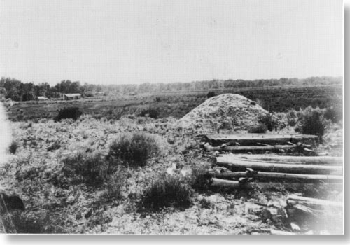 Historic photo of mound in sparsely vegetated area. House in far background.