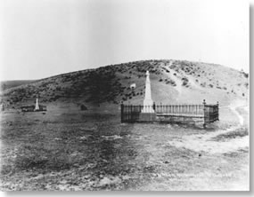 Historic photo of two wrought iron fence enclosed grave plots each with a tall monument.