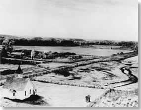 Historic photo with church in foreground and farmland behind.