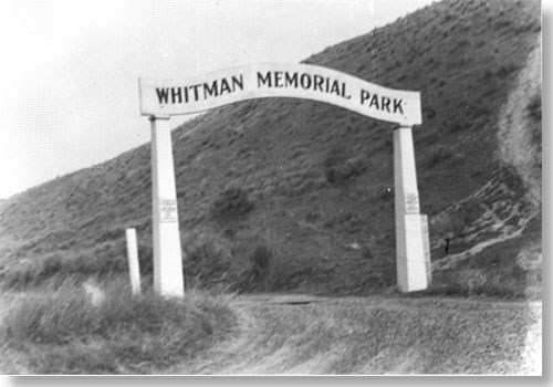 "Historic photo of arch over dirt road. Text on arch say, ""Whitman Memorial Park."""
