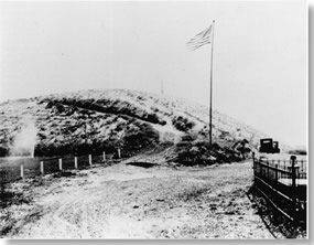 Historic photo of hill. Large flag pole at base of hill flying American flag. Two cars parked at base of hill.