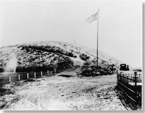 Historic photo of road leading up to hill. Large flagpole with American flag at base of hill. Cars parked near flagpole.