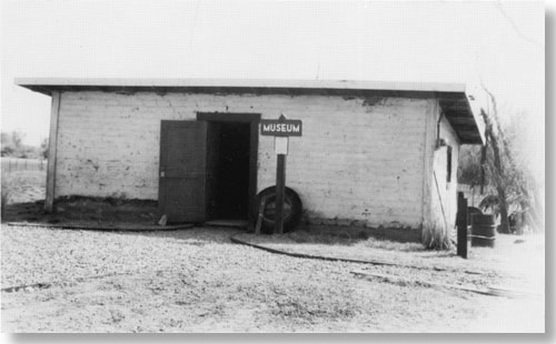 Historic photo of small, one story building. No windows on front wall. Wooden sign says