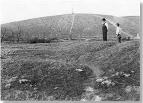 Two men standing on small rise looking down at lower land. No water in depression.