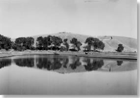 Millpond filled with water. Reflection of the hill and trees at the base of the hill can be seen on the pond's surface.