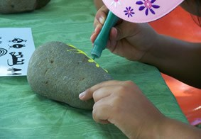 A young visitor paints Indian designs on a rock.