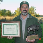 Bruce Hancock holds a certificate and a bronze statue of a bison that he was given for receiving this award.