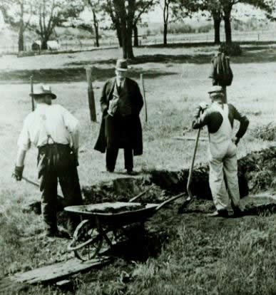Men with shovels and wheel barrow standing by hole.